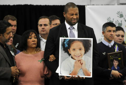 Newtown, CT 1/14/2013 Jimmy Greene, holding a photo of his daughter Ana Grace Marquez-Greene, who was killed in the Sandy Hook shootings, listens with family members as his wife speaks during the media conference . Behind him at right, Ian Hockley holds a photograph of his son Dylan, who was also killed in the media conference. One month after the tragic mass shooting at Sandy Hook Elementary School, a group of Newtown citizens have organized into a group called Sandy Hook Promise, to honor the lives of lost family and friends and committed to preventing similar tragedies from ever taking place again. The Group met at the Edmond Town Hall in Newtown.