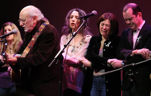 "Ridgefield, CT  02/10/13  Francine and David Wheeler (R) hold back tears as they sing ""We Shall Overcome"" with Peter Yarrow, his daughter Bethany (next to Francine) and Dar Williams (L) a concert at the Ridgefield playhouse Sunday afternoon. A ÒConcert of Caring, Healing and TogethernessÓ was co-organized by Operation Respect and Flagpole Radio Cafe, the later which the Wheelers are members of. The Wheelers lost their son Ben in the horrific massacre at Sandy Hook Elementary School last December. The concert was to help ""restoring the heart and soul of a caring community,"" and attended by familes who lost loved ones, first responders and residents of Newtown."