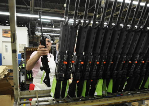 WEST HARTFORD, CT; 2/20/2013: Sergio Pereira adds a completed Colt rifle to a rack of newly assembled guns at the company headquarters in West Hartford. Each is then test fired, packaged, and sent to retailers.
