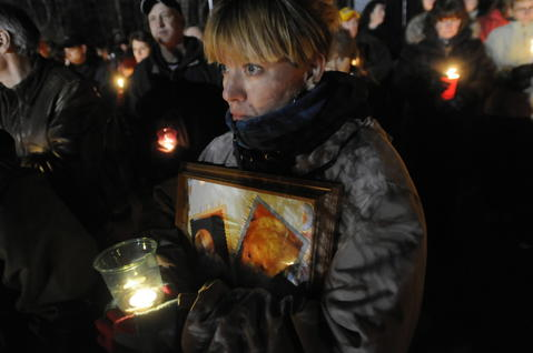 North Stoington, CT 3/1/2013 Melisse Fairbanks, cq, of New London, holds a candle and a framed montage of photos of Alton Perry, 2, and his six-month-old brother Ashton Perry, during a vigil to remember them at the recreation field on Rocky Hollow Road in North Stonington Friday night. The boys were shot and killed by their grandmother Debra Denison earlier in the week. Fairbanks, said she knows the boys father from bowling and used to watch the boys, was there to support the family. The crowed was large and people were being bussed to the location to easy traffic along route 2 as area residents, family and friends joined in a emotional tribute to the children full of prayers, singing, and testimonials.