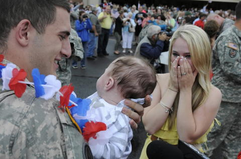 Windsor Locks, CT, 6/11/2013: Andrew Duhamel meets his son Landon, for the first time as his wife Brittany looks on after Duhamel arrived home from a year long deployment in Bahrain. The 248th Engineer Company in Norwich arrived home at the Army Aviation Support facility in Windsor Locks.