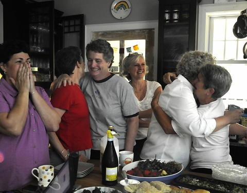 WEST HARTFORD, CT; 6/26/2013: Gathered in a kitchen of a West Hartford home, couples and friends celebrate minutes after 10 A.M. when the U.S. Supreme Court ruled that the Defense of Marriage Act unconstitutional. Reacting are from left, Carol Buckheit, of Avon, Tracy Wilson and her wife State Senator Beth Bye, of West Hartford, Jamey Bell of Bloomfield, Jamie Mills of Middletown and Beth Kerrigan of West Hartford.