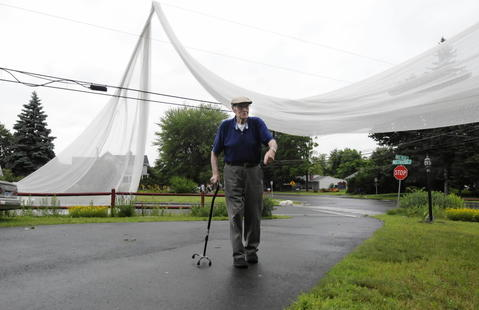 WINDSOR LOCKS, CT; 7/1/2013: Sebastian Fiume, 85, has his yard on South Center Street in Windsor Locks draped in tobacco netting as does many in his neighborhood after a violent storm ripped through the area Monday.
