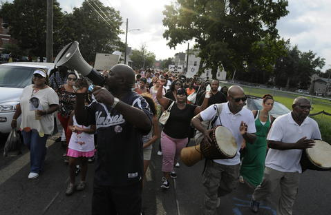 HARTFORD, CT, 7/22/2013: Several hundred march down Mather Street in Hartford during a rally to protest the verdict in the Trayvon Martin trial in Florida last week. Organizer of the event, Rev. Henry Brown, left, leads the marchers to the Old North Cemetery to the graves of black Union Army soldiers where the rally concluded.