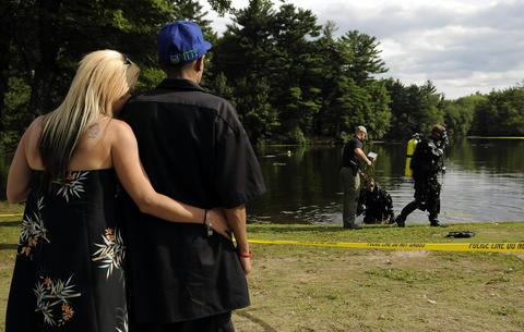 Bristol, CT  7/31/13  Nicole Tallarico and Frankie Colon of New Britain watch as members of the State Police dive team emerge after searching a perimeter area at Pine Lake in Bristol Wednesday afternoon as authorities continue their search for a weapon that could be linked to the Hernandez murder case. After three days of searching they have come up with no weapon or other evidence.