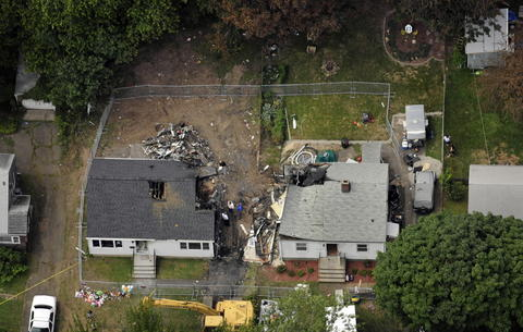 EAST HAVEN 08/12/13 Aerial views of the site on Charter Oak Avenue in East Haven show where a plane crashed into two houses, killing four people on Friday.  The debris of the plane has been removed but you can see how the leaves on the trees at the top of the photo were scorched by the extreme heat of the fire caused by the planes fuel. The houses are scheduled for demolition this week, maybe as early as Tuesday. A small makeshift memorial is seen in the lower left next to the crane that will knock down the homes.