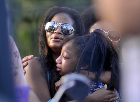 East Haven - 08/10/13 - Jonera Brantley, 13, of Waterbury, hugs her mother Lakeisha Lynch at a vigil at Margaret Tucker Park in East Haven Saturday evening.  Jonar is the stepsister of Sade Brantley, 13, one of the two girls who died inside their home at 64 Charter Oak Ave. in East Haven when a plane crashed into it Friday morning.