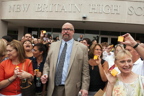 "2013.08.26 - New Britain, CT - New Britain Superintendent of Schools Kelt Cooper stands amid teachers outside New Britain High School before being photographed by former NBHS Principal Paul Salina as they held bars of soap symbolizing increased efforts to curb rude student behaivior. During his convocation speech earlier in the morning Cooper singled out cursing students and low slung pants as behaivors for which he had little tolerance. Calling it ""a new motto,"" the former Texas Superintendent Cooper proclaimed to students, ""Don't talk smack and don't show crack."""