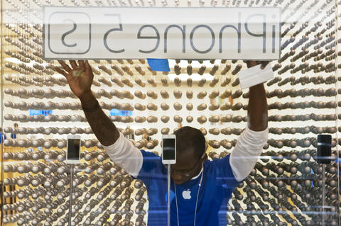2013.09.20 - Farmington, CT - An Apple Store employee affixes an iPhone 5S sign in the window of The Apple Store in Westfarms. Mall officials estimated 200 people waited in line before the store opened to buy the new iPhone.