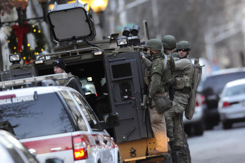 Police get on an armored car at College and Chapel Streets as officials sought a reported gunman at Yale University in New Haven Monday.
