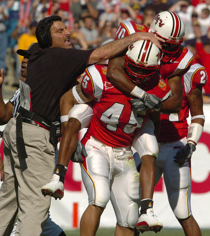 Terps assistant coach Dave Sollazzo (left) and safety Madieu Williams (right) congratulate Shawne Merriman after his first quarter fumble recovery.