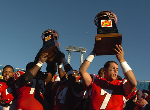 Terps quarterback Scott McBrien holds up the MVP trophy.
