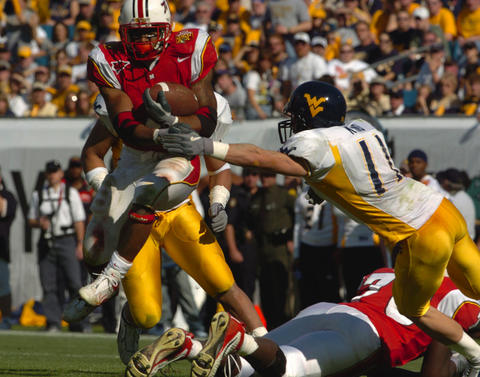 Terps running back Bruce Perry leaps over a teammate to gain a few more yards.