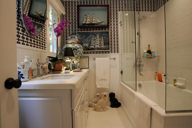 In Hartig's bathroom, white cabinets and marble counter tops are set off by bold wallpaper from Walnut in Los Angeles. Hartig's whimsical flourishes include antique scale-model schooners under glass, a trio of Staffordshire dogs and a Champagne bottle in the shower.