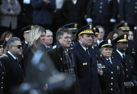 Cook County Sheriff Tom Dart, center, watches as the body of Cook County sheriff's officer Cuauhtemoc Estrada is taken into his funeral service at Holy Name Cathedral.