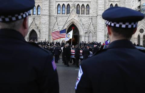 Officers watch as the body of Cook County sheriff's officer Cuauhtemoc Estrada is taken into his funeral service at Holy Name Cathedral.