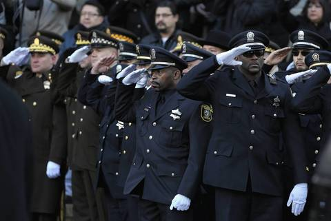 Officers salute as the body of Cook County sheriff's officer Cuauhtemoc Estrada is taken into his funeral service at Holy Name Cathedral in Chicago Saturday Dec. 28, 2013. Estrada was fatally shot in west suburban Bellwood on Dec. 20 after he intervened in an armed robbery that targeted his daughter and her boyfriend.