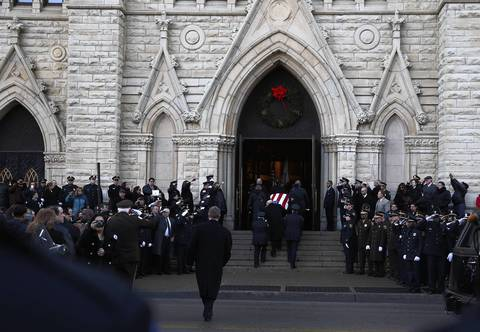 A crowd watches as the body of Cook County sheriff's officer Cuauhtemoc Estrada is taken into his funeral service at Holy Name Cathedral.