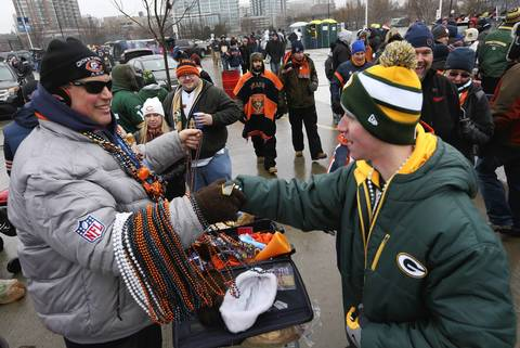 Ken Vedder, left, of Geneva, hands out beads to a Green Bay Packers fan, outside Soldier Field, before the game.