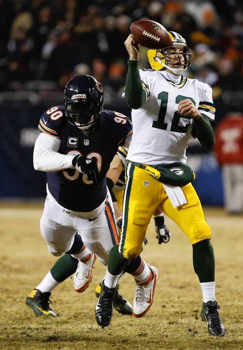 Chicago Bears defensive end Julius Peppers hits Green Bay Packers quarterback Aaron Rodgers (12) in the second quarter at Soldier Field. The ball was recovered by a Packers player for a touchdown on the play.