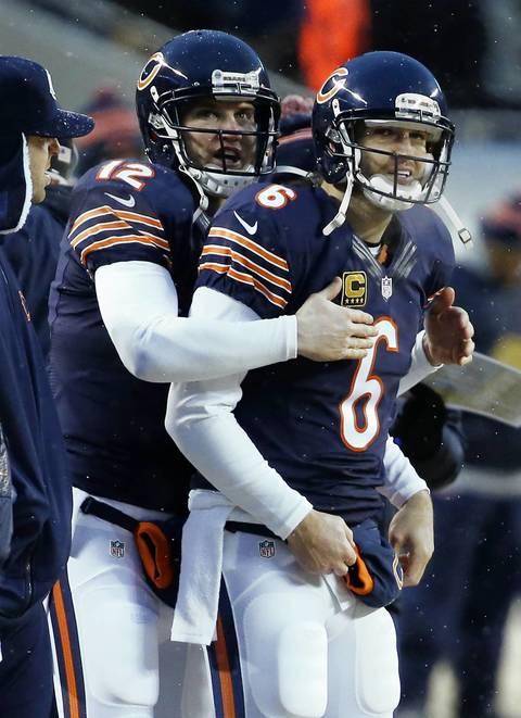 Chicago Bears quarterback Josh McCown (12) hugs Chicago Bears quarterback Jay Cutler (6) following a touchdown by Chicago Bears running back Matt Forte.