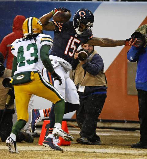 Chicago Bears wide receiver Brandon Marshall (15) tip toes down the side line after a catch as Green Bay Packers free safety M.D. Jennings (43) makes the tackle in the first quarter at Soldier Field.