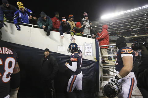 Jay Cutler hands a kid a souvenir towel while leaving the field after his team's loss.