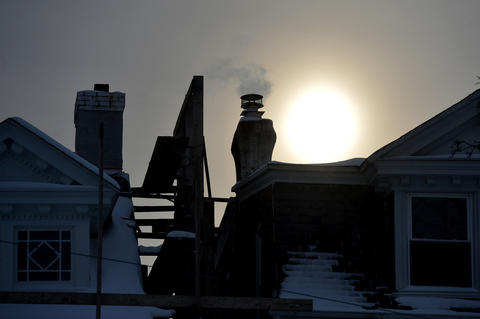 A glowing sun reveals smoke coming from a chimney of a home in Emmaus on Friday, January 3 during the first snow storm of 2014.