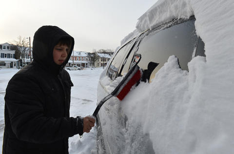 """I kindof like snow days, but then I kindof don't like snow days cause they take a day off in the summer"" laments Corey Edelman, 10, of Emmaus as he cleans off his mother's vehicle on Friday, January 3 during the first snow storm of 2014 in Emmaus."