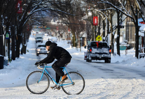 A man on a bicycle rides through the snow passing Chestnut Street in Emmaus during the morning on Friday, January 3 during the first snow storm of 2014.
