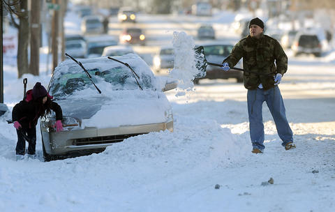 Carlos Rodriguez of Allentown (right) and his daughter Brianna Rodriguez 8, of Bethlehem (left), help dig out her mothers car along Broad Street in Bethlehem on a breezy Friday afternoon.