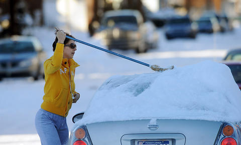 Norma Jean of Bethlehem clears off her car along 10th Ave. with a broom as she gets ready for work on a breezy Friday afternoon.