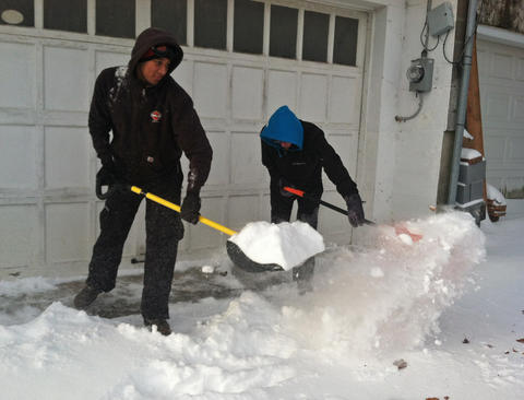 Emmaus residents work to clear their sidewalks of snow early Friday morning as the first snow of 2014 moved through the Lehigh Valley.