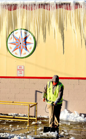 """Lee Lindner of Allentown who works for the Allentown Farmers Market clears snow at one of the entrances to the facility Friday. A snowstorm left about 6 - 8"""" in the Lehigh Valley."""