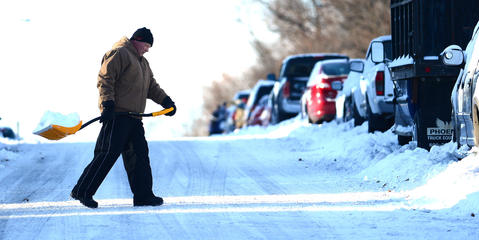 """A man carries another shovelfull of snow away from his home as he clears his walkway along Lehigh Parkway South early Friday. A snowstorm left about 6 - 8"""" in the Lehigh Valley."""