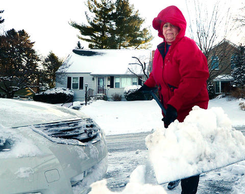 "Ann O'Keefe of Allentown clears snow from her car and parking space along Lehigh Parkway South early Friday. A snowstorm left about 6 - 8"" in the Lehigh Valley."