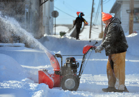 "George Owens, of Emmaus uses a snowblower to clear the area around his home in Emmaus during the morning on Friday, January 3 during the first snow storm of 2014. ""Soon this will melt anyway"" he says as he takes a brief break. ""I'm almost done here."""