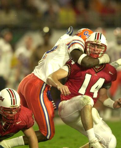 Maryland quarterback Shaun Hill is hit by a Florida defender after getting the ball away.