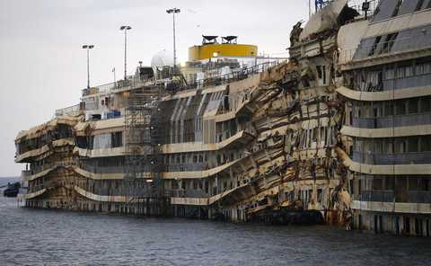 "The cruise liner Costa Concordia is seen during the ""parbuckling"" operation outside Giglio harbour January 11, 2014. Thirty massive tanks filled with air will lift the hulk of the Costa Concordia off the seabed in June so it can be towed away from the Italian island of Giglio where it capsized two years ago, officials said on Friday. The 114,500-tonne vessel hit rocks on Jan. 13, 2012, killing 32 people. It was hauled upright in a complex ""parbuckling"" operation in September but still rests where it capsized, just outside the holiday island's small port. Refloating the Concordia will be one more phase in the largest maritime salvage in history. Where the ship will be dismantled - the final step - has yet to be decided."
