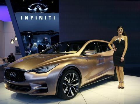 A model poses next to the Infiniti Q30 concept car during the press preview day of the North American International Auto Show in Detroit, Michigan January 14, 2014.