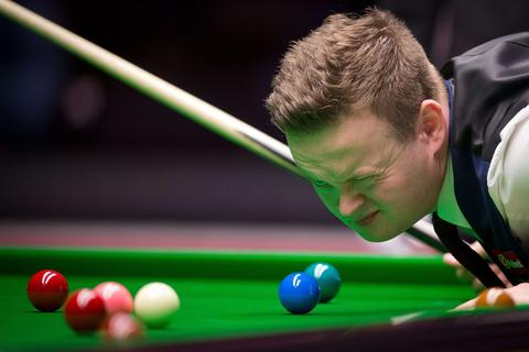England's Shaun Murphy measures a shot during his first round match against China's Ding Junhui on day three of the Masters Snooker tournament at Alexandra Palace in London on January 14, 2014.
