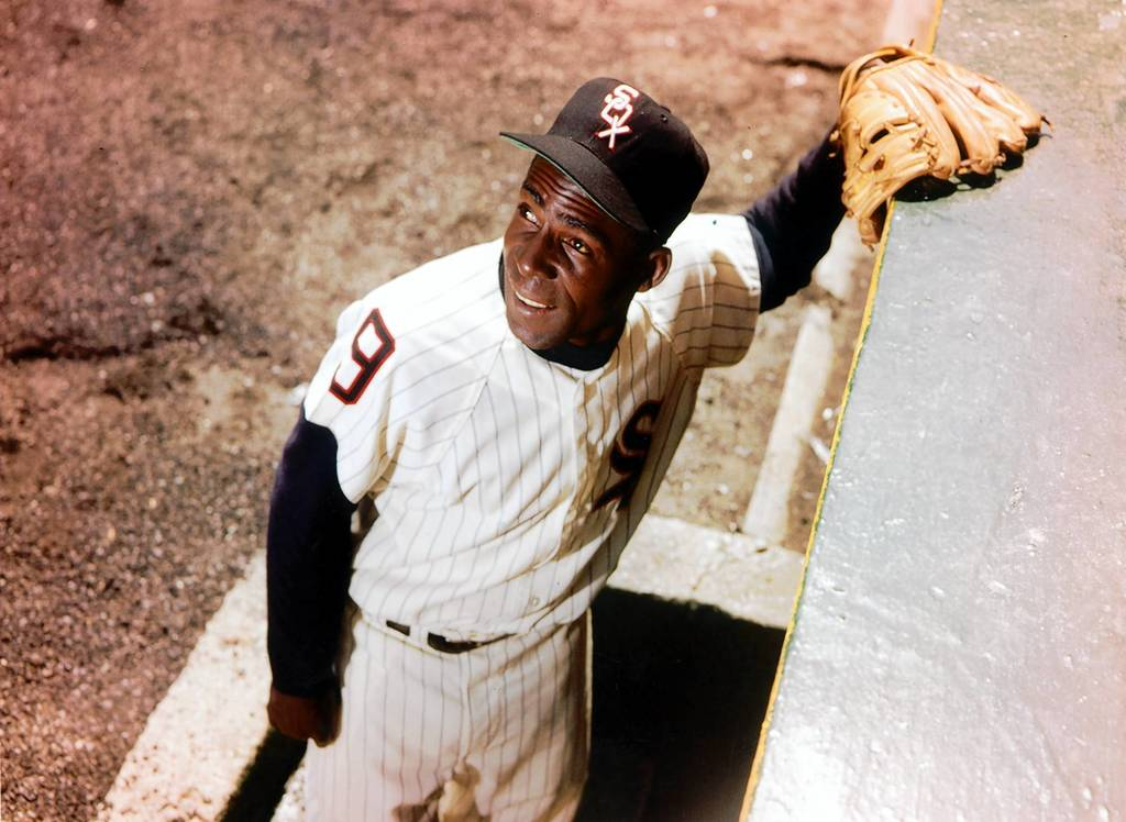 White Sox outfielder Minnie Minoso poses outside the Comiskey Park dugout on Sept. 3, 1960.