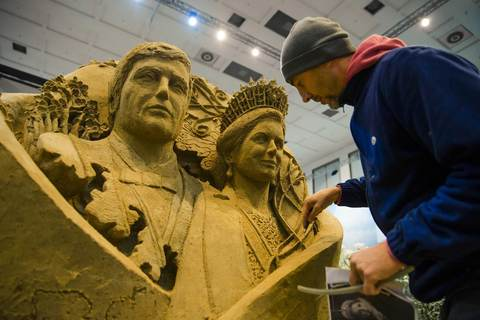 An artist puts finishing touches to a sand sculpture of Netherlands' King Willem-Alexander and Queen Maxima at the Dutch pavilion during preparations for the Green Week international food, agriculture and horticulture fair in Berlin, January 16, 2014.