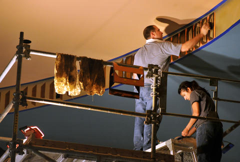 Tim Phebus and Elisha Rowe, of Thomas Moore Studios, use a stencil to paint on the ceiling return in the main auditorium.