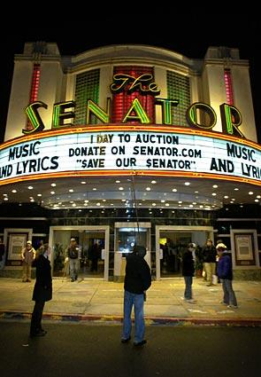 Senator Theatre manager Austin Crise, center, changes the message on the marquee late Monday evening to announce that foreclosure of the historic art deco movie house may be one day away.