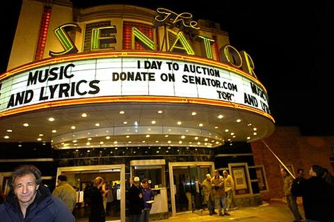 Senator Theatre manager Austin Crise, at far right, changes the message on the marquee late Monday evening to announce that foreclosure of the historic art deco movie house may be one day away.