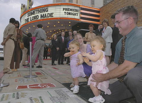 "Eighteen-month-old twins Brooke (left) and Kera Gaigler, who appear in the movie ""Something the Lord Made,"" look with their parents Valerie and Chuck Gaigler of Ellicott City  at the sidewalk square honoring the film outside of the Senator Theatre."