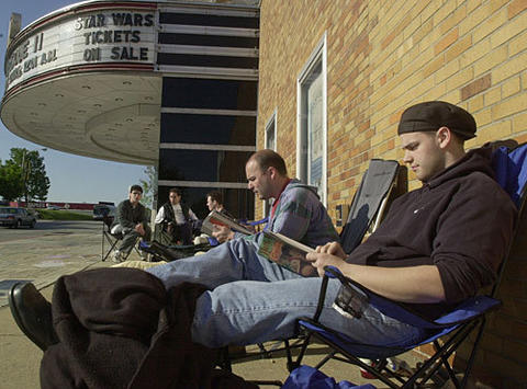 "Two fans camp out overnight to secure seats for the premiere of ""Star Wars Episode II"" at the Senator Theatre."