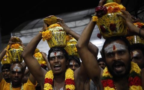 Devotees carry milk jugs during Thaipusam festival in Singapore early January 17, 2014. Thaipusam is a Hindu festival observed on the day of the full moon during the Tamil calendar month of Thai, and celebrated in honour of the Hindu god Lord Murugan.