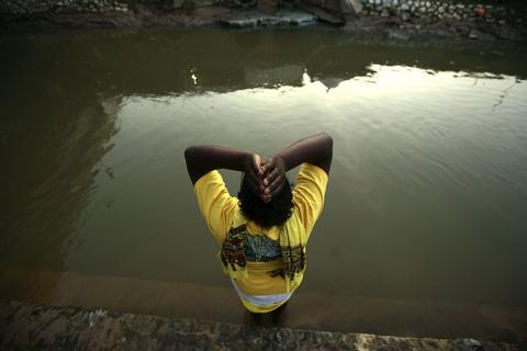 A Hindu devotee performs prayers near a river before beginning his pilgrimage to the sacred Batu Caves temple during Thaipusam festival at Batu Caves, near Kuala Lumpur January 16, 2014. Thousands of Hindus, who comprise over eight percent of the 29 million Malaysian population, participate in the annual Hindu thanksgiving festival in which devotees subject themselves to painful rituals in a demonstration of faith and penance held in honour of Lord Subramaniam. Thaipusam will be held on January 17.